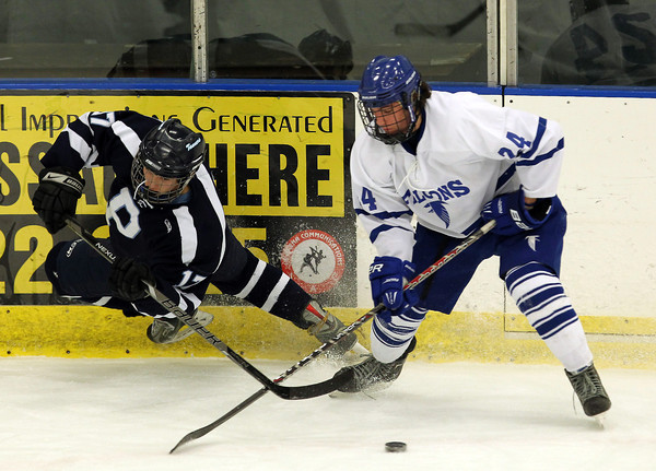 Peabody forward Erik Hennessey, left, goes careening into the boards after tripping over Danvers forward Adam Merry, right, as they battled for possession of the puck on Wednesday evening. David Le/Staff Photo