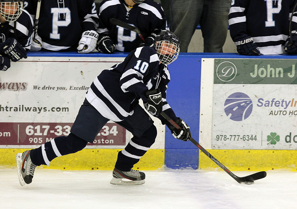 Peabody sophomore forward Ryan Carney keeps his head up and looks for an open teammate in front of the Peabody bench during the first period of play on Wednesday evening against Danvers at the Rockett Arena. David Le/Staff Photo