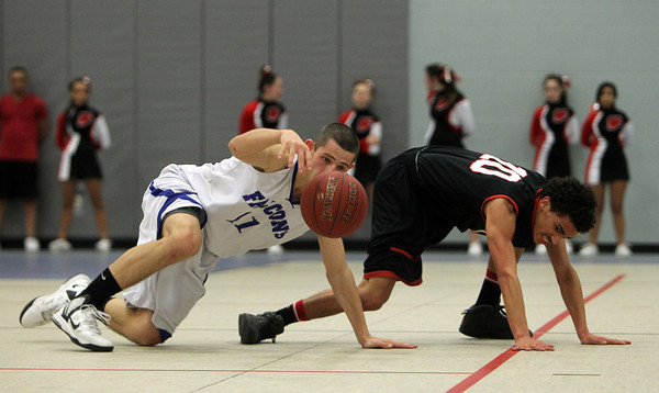 Danvers: Danvers senior guard Eric Martin, left, tries to keep his dribble after a steal attempt from Salem junior guard Marvin Baez, right. Martin and the Falcons took down the Witches 66-44 on Friday evening in NEC action. David Le/The Salem News