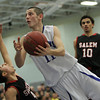 Danvers: Danvers senior captain Eric Martin, right, is fouled by Salem's Emilio Beato, left, on his way to the basket. Martin and the Falcons defeated the Witches 66-44 on Friday evening in front of a packed house at Danvers High School. David Le/The Salem News
