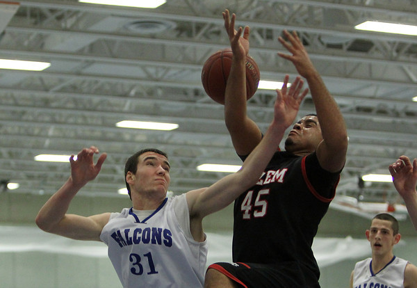 Danvers: Danvers senior captain Dan Connors, left, and Salem senior Jared Louf-Woods battle for a rebound under the basket in the first half of play on Friday evening. David Le/The Salem News