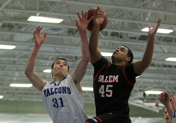 Danvers: Danvers senior forward Dan Connors, left, and Salem senior Jared Louf-Woods, right, battle for a rebound during the first half of play. Connors and the Falcons defeated the Witches 66-44 in NEC action on Friday evening. David Le/The Salem News