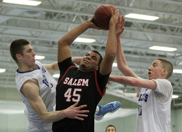 Danvers: Salem High School senior forward Jared Louf-Woods, center, grabs a rebound while surrounded by Danvers senior forward Nick Bates, left, and sophomore guard Vinny Clifford. The Falcons played stifling defense all night and defeated the Witches 66-44 on Friday evening. David Le/The Salem News