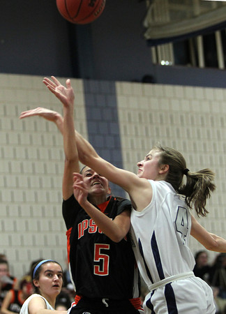 Hamilton: Ipswich sophomore guard Masey Zegarowski, left, flips the ball up towards the hoop while being fouled hard by Hamilton-Wenham junior Haley Willis, right. Zegarowski scored 26 points and added 5 assists to lead the Tigers past the Generals on Friday evening. David Le/Salem News