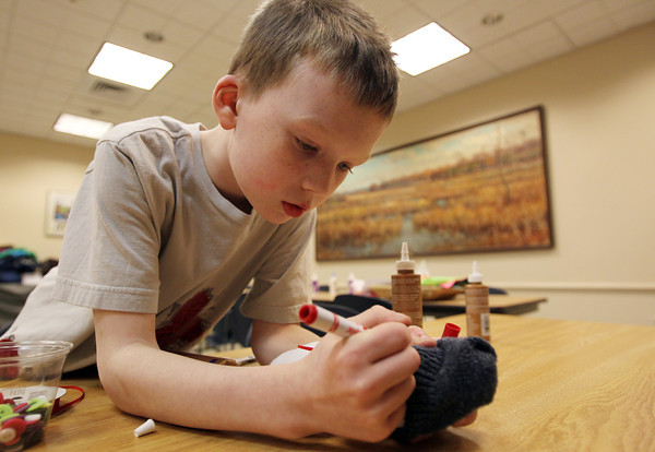 Ipswich: Jacob Paquette, 7, of Ipswich, draws eyes on his snowman puppet at the Ipswich Public Library on Thursday afternoon during an arts and crafts workshop. David Le/Salem News