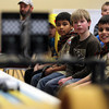 Hamilton: From left, Boy Scouts Alex Johnson, 10, Jack Wieman, 9, and Alex Gujral, 10, of Hamilton, watch as their race cars fly across the finish line in the finals of the Boy Scouts annual Pinewood Derby at the First Congressional Church of Hamilton on Saturday afternoon. David Le/The Salem News