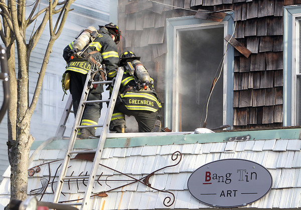 Marblehead: Marblehead firefighters work in tandem on the roof of the Bang Tin Art Gallery on Pleasant St. A fire broke out on the left side of the building around 3:30 on Thursday afternoon. David Le/Salem News