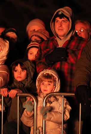 Salem: Eight year old Eddie Rowley, left, of Salem, and Bill Waters with his daughter Ella, 6, also of Salem, watch Christmas trees burn at Dead Horse Beach during the 10th Annual Christmas Tree Bonfire on Friday evening. David Le/Salem News