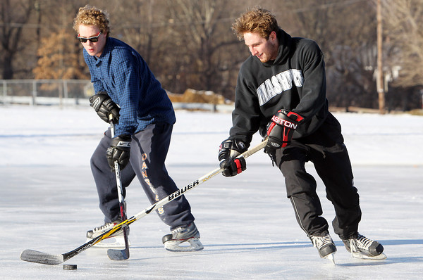 Tucker White, right, and Bill MacKenzie, both 20 of Hamilton, play pickup hockey on the frozen pond at Patton Park in Hamilton on a cold Thursday afternoon. David Le/Staff Photo