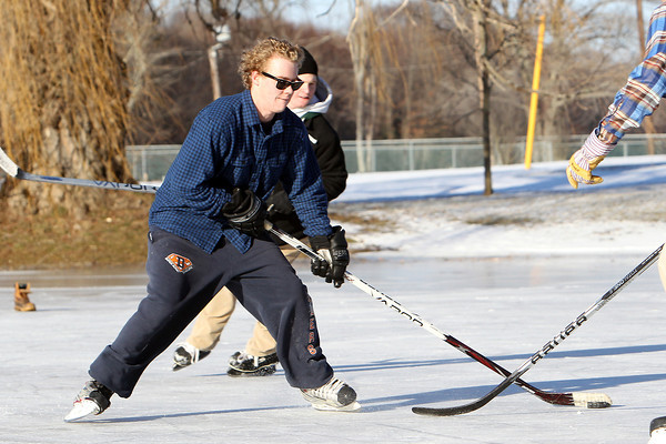Bill MacKenzie, 20, of Hamilton, dangles with the puck while playing pickup hockey on the frozen pond at Patton Park in Hamilton on Thursday afternoon. David Le/Staff Photo