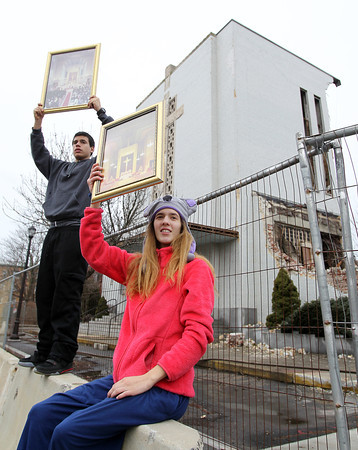 Salem: Seventeen-year-old Gabriel Duzz and twenty-year-old Alyse Reardon, both of Salem, hold up photographs of St. Joseph Church while protesting the demolition along Lafayette St. on Saturday afternoon. David Le/The Salem News