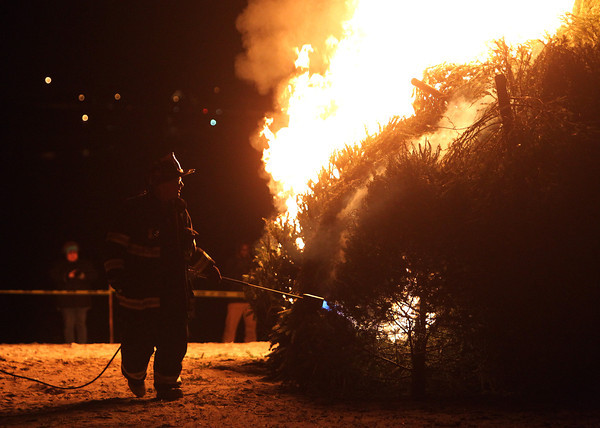 Salem: Smoke and flames spew from a large pile of Christmas trees as Salem firefighter Jon Thomas lights them on fire at the start of the 10th annual Christmas Tree Bonfire at Deadhorse Beach on Friday evening. David Le/Salem News