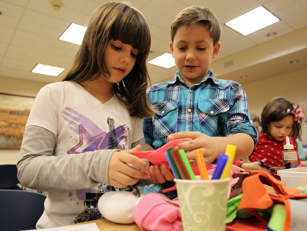 Ipswich: Nine-year-old twins Wesley and Cassidy Smith, of Ipswich, decorate snowman puppets at an arts and crafts afterschool program held at the Ipswich Public Library on Thursday afternoon. David Le/Salem News