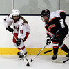 Gloucester: Masco forward Catherine Headrick, left, tries to control the puck while being pursued by Beverly's Rachel Trocchi, right, during the first period of play on Saturday evening. David Le/The Salem News