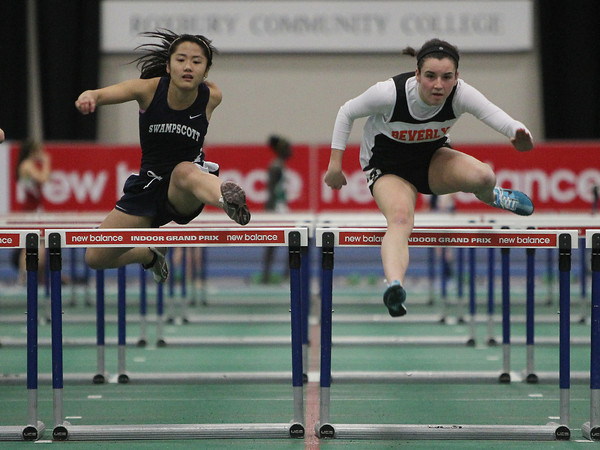 Boston: Beverly High School junior Kristen O'Connor, right,  clears the last hurdle and outraces Swampscott senior Vy Le to the finish line during the finals heat of the high hurdles during the NEC Indoor Track Championships at the Reggie Lewis Center in Boston. David Le/Salem News