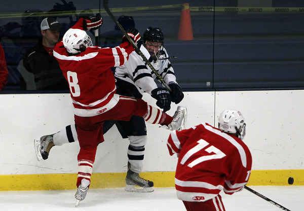 Peabody: Peabody High School senior defenseman Pat Ruotolo, right, and Saugus sophomore forward Chris Sanderson, left, collide along the boards as the puck squirts away during the first period of play on Wednesday evening at the McVann-O'Keefe Rink. David Le/Salem News
