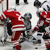 Peabody: Peabody High School senior goalie Joe Powers, left, keeps his eyes on the puck as it bounces around the crease and makes a save against Saugus on Wednesday evening. David Le/Salem News