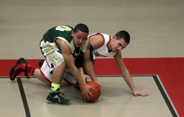 Salem: Salem High School senior guard Billy Muse dives on the floor and fights for a loose ball with Lynn Classical senior Victor Mercado, left, during the second quarter of play on Friday evening. David Le/Salem News