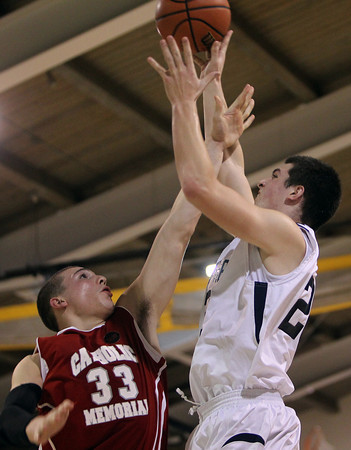 St. John's Prep sophomore forward Jake Burt, right, shoots a jump shot over Catholic Memorial senior Rich Lopez, left, during the first half of play on Tuesday evening. David Le/Salem News
