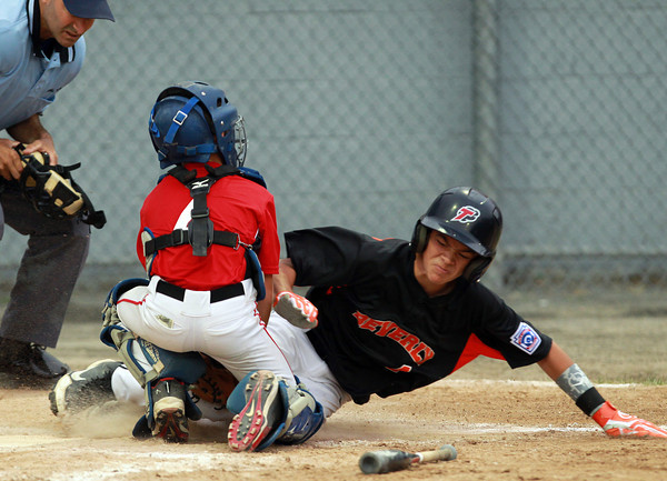 Lynn: Beverly's Clayton McCalpine, right, gets tagged out at home plate by North Andover East catcher Robbie Carpenter as he tried to advance on a safety squeeze. David Le/Salem News