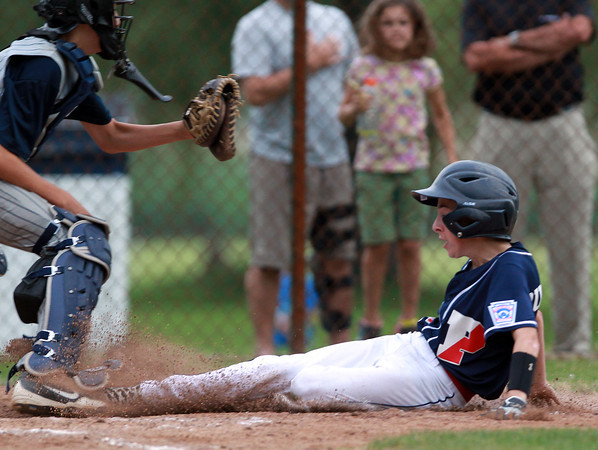 Nahant: Peabody West baserunner Chris Ruggiero slides safely into home on an RBI triple by Nick Iannuzzi, as Lynnfield catcher Jagger Benson waits for the throw. David Le/Salem News