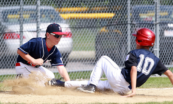 West Roxbury: Peabody West third baseman Cooper Jacques (16) applies a tag to sliding Holden runner Tyler Nguyen, right, but is just late as Nguyen managed to get his foot on the bag. David Le/Salem News