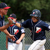 West Roxbury: Peabody West first baseman Dan Marshall (15) wears a big smile on his face as he gets a high five from third base coach Ed Aiello after Marshall launched a grand slam off the left-centerfield scoreboard to break an 8-8 tie with Holden on Saturday afternoon. David Le/Salem News