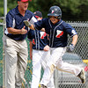 West Roxbury: Peabody West first baseman Dan Marshall (15) smiles as he gets a high five from third base coach Ed Aiello after Marshall hit a grand slam in the top of the 4th inning to break an 8-8 tie and give Peabody West a lead they would not relinquish, going onto beat Holden 20-10 in 5 innings. David Le/Salem News