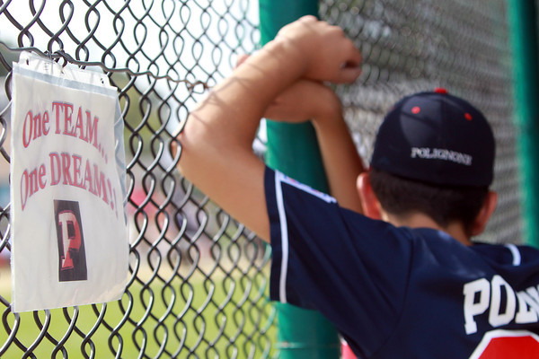 West Roxbury: A sign hangs in the Peabody West dugout next to Jonathan Polignone as he watches the action on the field on Saturday afternoon. David Le/Salem News