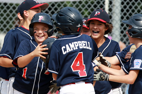 West Roxbury: Peabody West All-Stars Dom Lewis (1), left, Ed Campbell (4), and Nick Iannuzzi (7), right, mob teammate Dan Marshall at home plate after he smashed his first home run of the season, a grand slam off the scoreboard in left-centerfield, to give the Tanner City All-Stars a 12-8 lead in the top of the 4th inning. David Le/Salem News