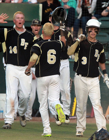 Lynn: Bishop Fenwick junior Eric Razney gets greeted by his teammates after he scored the Crusaders' first run of the game against St. Mary's on Wednesday evening. David Le/Salem News
