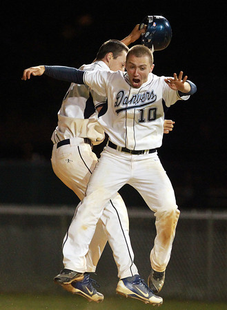 Marblehead: Danvers High School seniors Joe Strangie, right, and Dan Connors, leap high in the air after Connors dropped down a successful suicide squeeze bunt to give the Falcons an extra inning walk-off win over Reading on Tuesday evening. David Le/Salem News