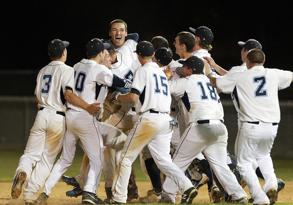 Danvers: The Danvers High School baseball team mobs senior Dan Connors after he laid down the successful suicide squeeze bunt to give the Falcons a 7-6 walk off win over Reading on Tuesday evening. David Le/Salem News