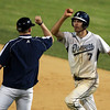 Danvers: Danvers senior Dan Connors gets a congratulatory fist bump from the first base coach after he drove in the game tying run in the bottom of the 7th inning. In the bottom of the 9th, Connors laid down a successful suicide squeeze bunt, to score fellow senior AJ Couto, and send the Falcons home with a dramatic 7-6 come from behind victory. David Le/Salem News