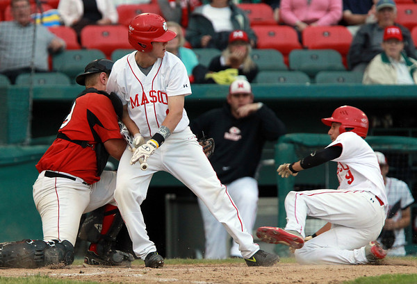 Brockton: Masco senior Greg Jain (9), right, slides into home plate, as Hingham catcher David Hutchins (49), left, moves around Masco junior Will Twiss (6), center, to tag Jain out on a failed suicide squeeze play. David Le/Salem News