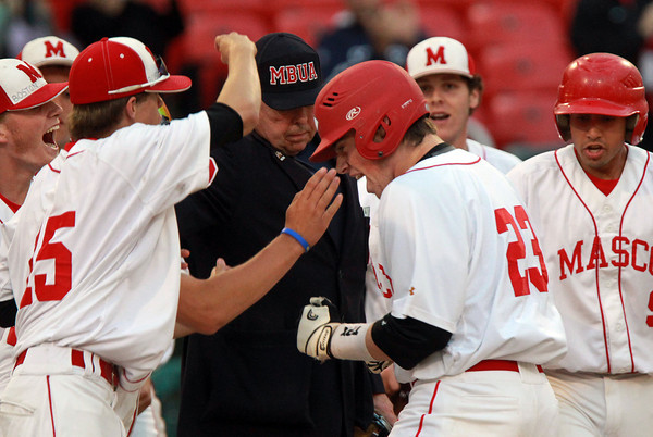 Brockton: Masco junior Joe Klingensmith (23) gets met at home plate by his teammates after blasting a solo home run to left field in the top of the 4th inning to tie the game at 1-1 against Hingham. David Le/Salem News