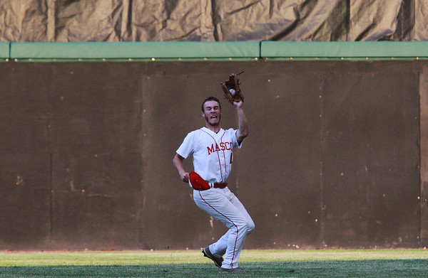 Brockton: Masco junior Tom Budrewicz (11) tracks down a fly ball while holding his hat to shield from the blinding sun. David Le/Salem News