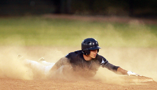 Lynn: Peabody left fielder Steven Leavitt (11) slides through a swirling cloud of dust and safely into second base after a successful steal attempt against St. John's Prep in the Division 1 North Semifinal. David Le/Salem News