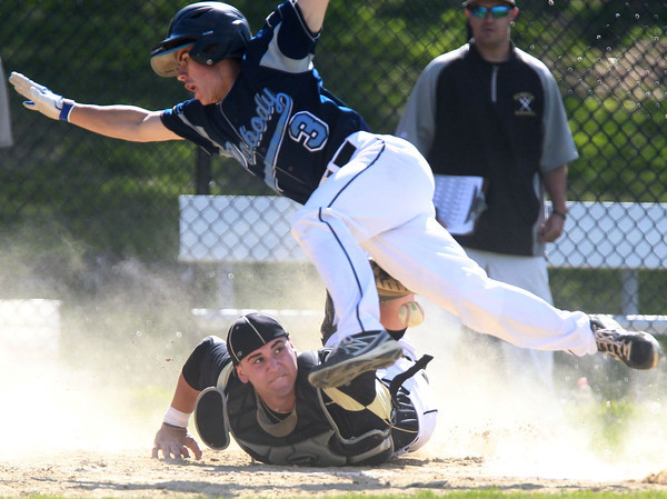 Peabody: Peabody shortstop Ryan Collins goes airborne as lunging Bishop Fenwick catcher Gianni Esposito cannot hang onto the ball on a close play at home plate. David Le/Salem News
