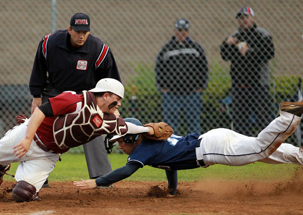 Danvers: Danvers senior Joe Strangie lunges to touch home plate, but Gloucester catcher Jordan Pallazola dives and applies the tag just in time to record the out on a close play. David Le/Salem News