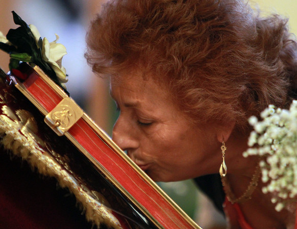 Peabody: Soula Hoxha, of Topsfield, kisses a the bible laid in a representation tomb for Jesus Christ following a Good Friday ceremony at St. Vasilios Greek Orthodox Church on Friday afternoon. David Le/Salem News