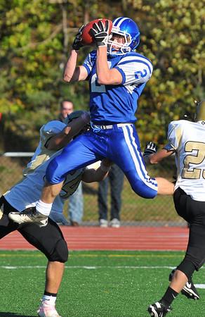 Peabody: Georgetown's Derek Depasquale leaps to make a catch between two Bishop Fenwick defenseman during Saturday's 25-14 Georgetown win .   Staff photo / Mark Teiwes