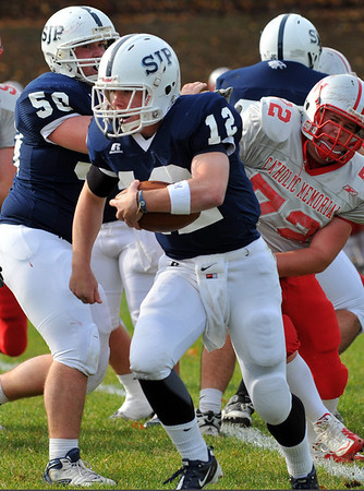Danvers: St. John's Prep quarterback Tommy Gaudet gains some yards on a run past the Catholic Memorial defensive line.  photo by Mark Teiwes / Salem News