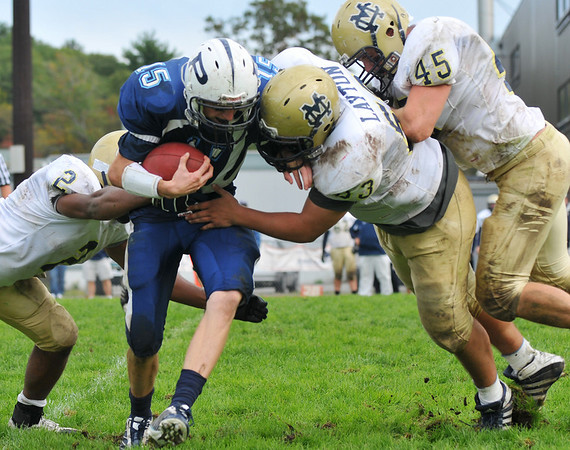 Peabody: After gaining some yards, Peabody quarterback Jason Hiou, center, gets tied up by three Malden Catholic defenseman.