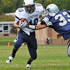 Hamilton: Triton High School varsity football player Matt Hill, left, makes a run gaining yardage as Hamilton-Wenham defenseman Alton Bynum attempts a tackle. photo by Mark Teiwes / Salem News