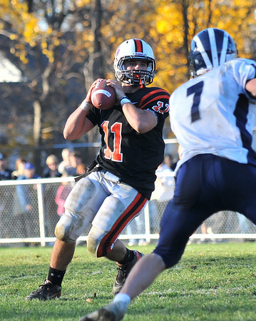 Beverly: Beverly quarterback Joe Wioncek scans the field for a pass as he is pressured by the Swampscott defense. photo by Mark Teiwes / Salem News