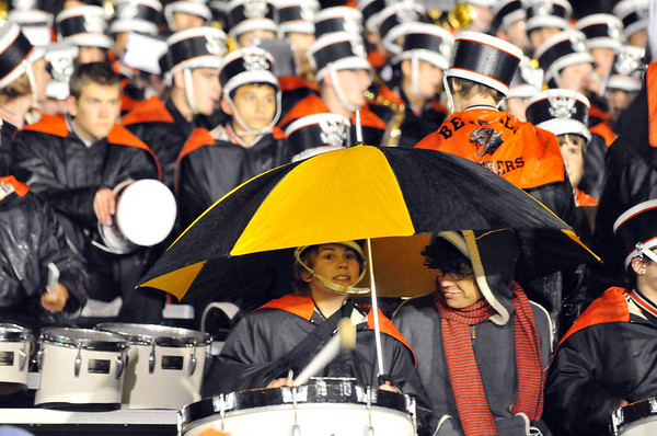 Beverly: Beverly marching band bass drummer Olivia Burnham, left, gets shelter from the rain when her friend Gabe Lozada with a large umbrella during Friday night's football game.   photo by Mark Teiwes / Salem News
