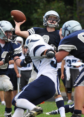 Hamilton: Hamilton-Wenham Regional H.S football quarterback Keith Dylan, center, launches a pass during a game against Triton. photo by Mark Teiwes