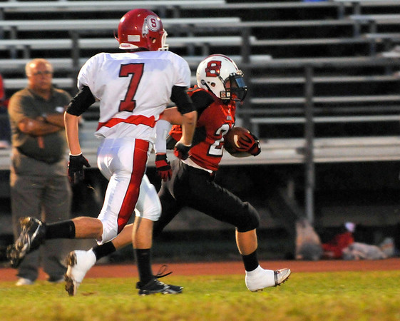 Salem: Chris Bozarjian, right, flies past a Saugus player Stephen Almquist to score a touchdown on the opening kickoff. photo by Mark Teiwes / Salem News
