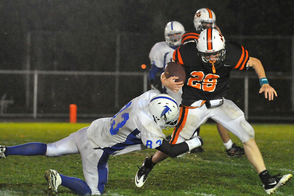 Beverly: Beverly's Kenny Pierce, right, is slowed by Danvers' Patrick McBride diving to trip up Pierce.  photo by Mark Teiwes / Salem News